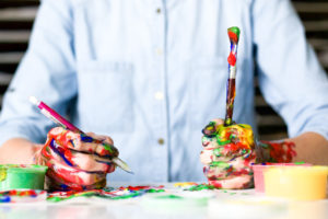 A person holding two paintbrushes, their hands dirty with color.